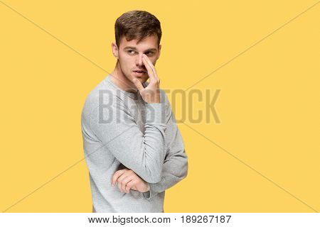 The young serious man looking cautiously on yellow studio background and Speaking secret to camera