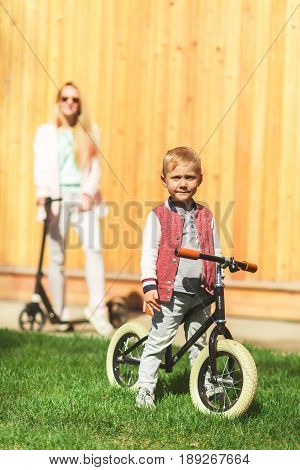 Photo of woman with boy at wooden wall on skooters in park