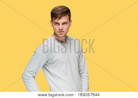 The young serious man looking cautiously on yellow studio background