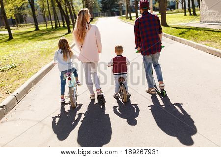 Photo from back of young family with children in park
