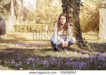 Young Woman Crouching On A Spring Flower Meadow
