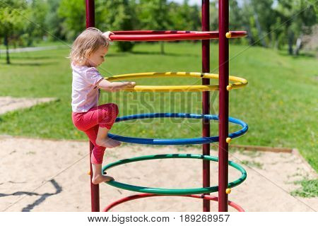 Adorable Little Girl Enjoying Her Time In Climbing Adventure Park On Warm And Sunny Summer Day. Summ