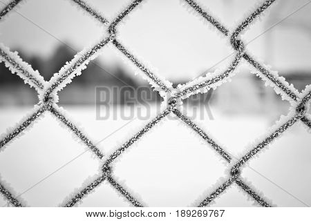 Closeup of frosty fence showing frost-details and some trees far in the distance