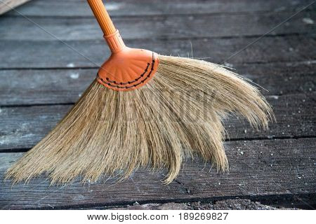 The broom is made of flowering grass sweeping dust and dirt on wooden floor.