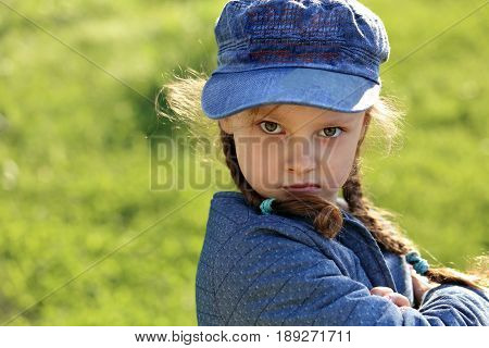 Angry Serious Kid Girl In Blue Hat Grimacing On Summer Green Grass Background. Closeup Portrait