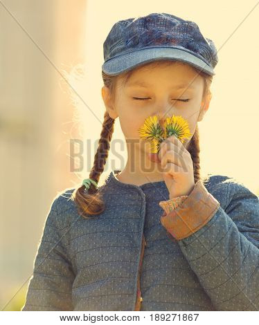 Beautiful Kid Girl In Blue Hat Smelling Yellow Dandelions With Closed Eyes On Sunny Summer Backgroun