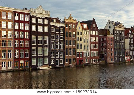 Beautiful Colorful Panarama View Of Old Amsterdam Buildings Near The River Under Blue Sky In Dusk Li