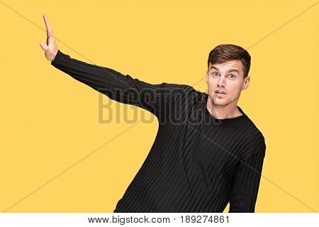 The young man pointing to something and looking at camera on yellow studio background
