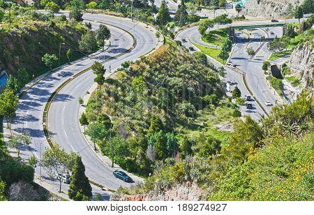 Impressive roads in La Paz, Bolivia together with some green vegetation.