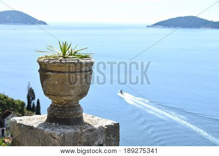 stone pots clanging and the background of blue sea horizon