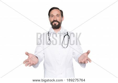 Cheerful Bearded Doctor In White Coat With Open Hands Looking At Camera Isolated On White
