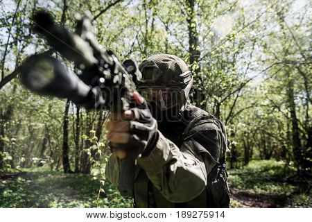 Sniper with submachine gun aiming at task in forest