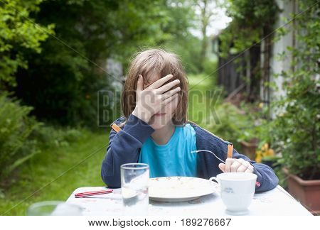 Young Boy Covering his Face Eating Outdoors