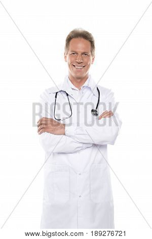 Smiling Middle Aged Doctor In White Coat And Stethoscope On Neck With Crossed Arms Isolated On White
