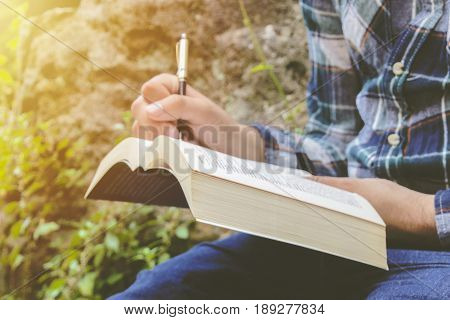 Male hand writing on paper. A man hand is write something. Writing notes in a notebook. Photo stock.
