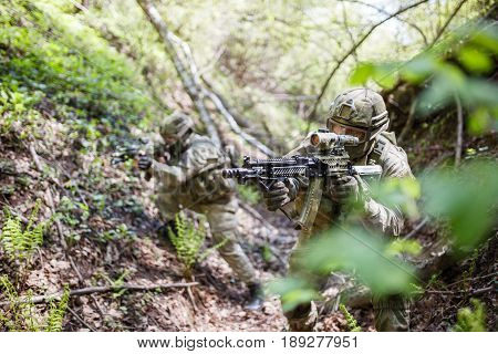 Two soldiers with machine guns stand in ravine among trees