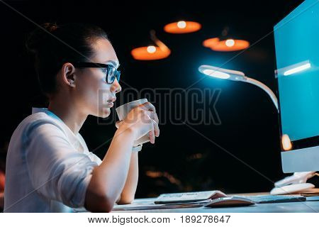 Side View Of Young Businesswoman In Eyeglasses Holding Cup While Working Late In Office