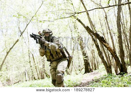 One soldier with submachine gun in forest on reconnaissance