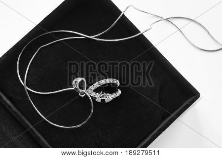 Black crystal pendant with diamonds in black jewel box closeup poster