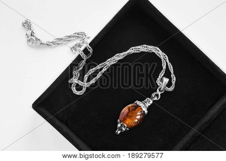 Vintage amber pendant on a chain in black jewel box closeup