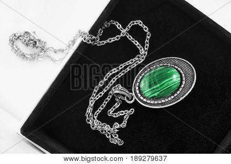 Vintage malachite medallion on silver chain in jewel box closeup