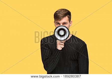 The young man holding a megaphone on on yellow studio background
