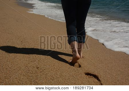 Bare feet of a women moving forward along the seashore