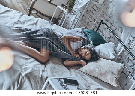 Peaceful sleep. Top view of attractive young woman covered with blanket keeping eyes closed and smiling while lying on the bed at home