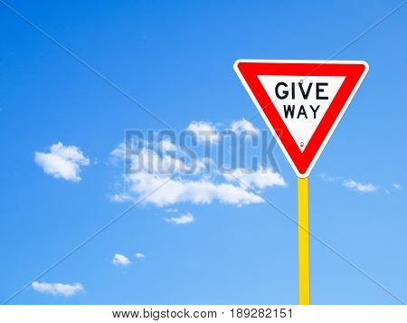 Give way sign on blue sky background (with clipping path)