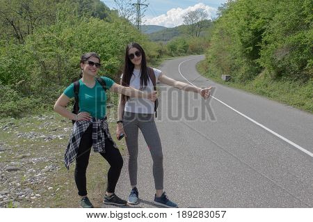 Hiking sticks near me - hitchhiking. Trekking together. Tourists hitching a ride