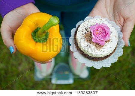 The fat woman is standing on the scales wants to lose weight diet the top view in a blue suit on the green grass selects a yellow big sweet bell pepper or round brown with a white cake with a rose of pink color holding them in hands with short blue nails
