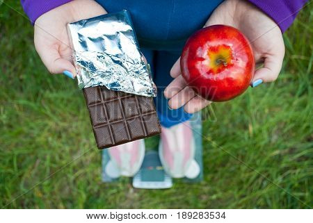 Fat woman wants to lose weight diet top view in blue suit stands on transparent glass scales in pink sneakers on green grass selects red big apple or chocolate bar in foil chocolate keeps them in hands with short blue nails on blurred background
