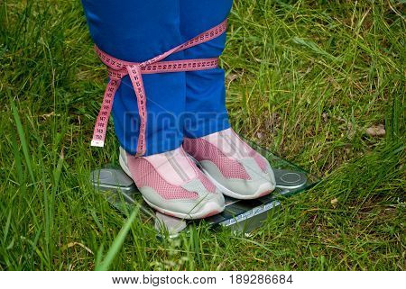 Sport sportswoman fat woman lose weight standing left sideways on the scales legs connected pink measuring tape numbers blue sports trousers knee-deep in pink sneakers glass transparent scales side view on green grass blurred background