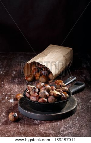 Roasted edible chestnuts served in cast iron skillet on dark wooden table. Copy space.