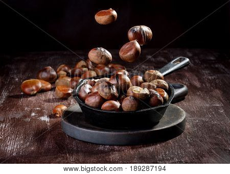 Roasted edible chestnuts served in cast iron skillet on dark wooden table. Flying / levitation food.