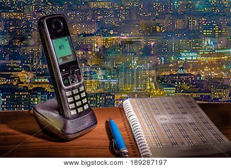 Touchscreen phone on the background of evening city. Lying next to a Notepad to record numbers and a blue pen.