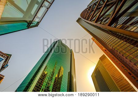 Tokyo, Japan - April 20, 2017: Sky High-rise Facade reflecting. Panoramic wide angle view and perspective to steel light background of glass high rise buildings of Shiodome in Shimbashi. Sunset light.
