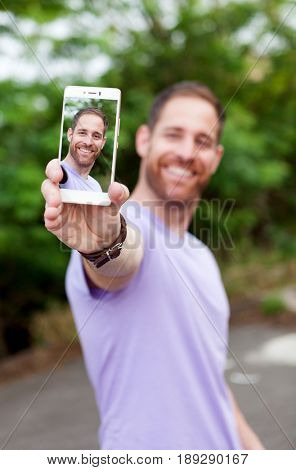 Casual guy in a park taking a photo with his mobile. Focus in the mobile