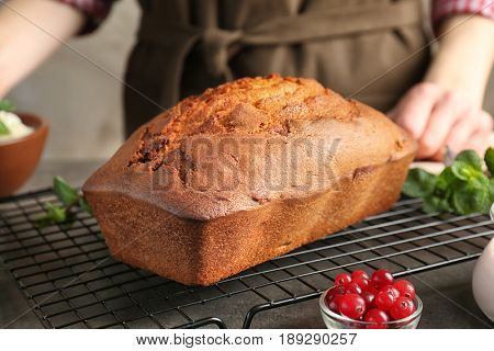 Cooling grid with freshly baked yogurt cake and woman on background
