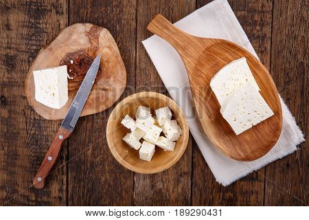Sliced fresh brined white cheese from cow milk on wooden table. Top view.