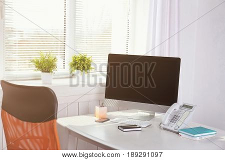 Modern comfortable workplace with computer and window blinds