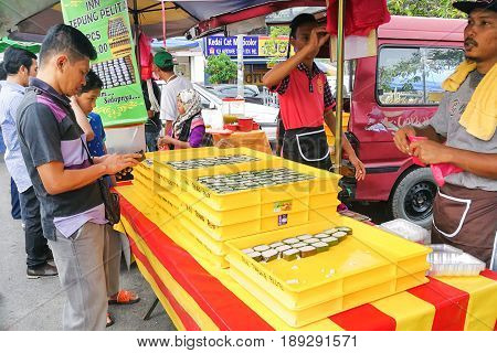 KUALA LUMPUR MALAYSIA June 2 2017: Muslim shopper buying sweet desserts from street stall vendor for breaking fast or iftar