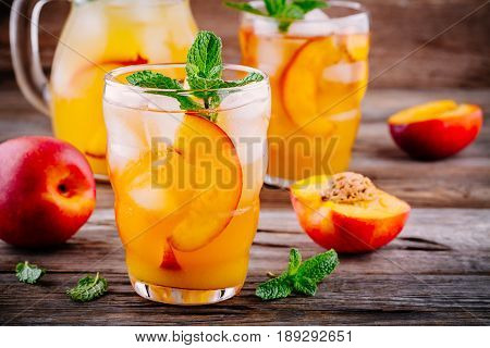 Summer Cold Drinks: Homemade Peach Ice Tea With Ice Cubes, And Mint In Glasses