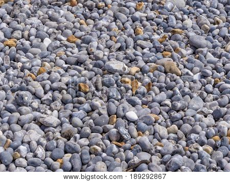 Background of smooth pebbles in different colors and sizes on the beach