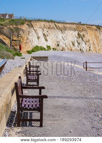 Benches on beach of Isle of Wight in summer England UK. Focus on first bench.