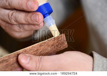 Carpenter glueing merbau wood detail by hands closeup