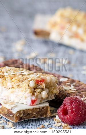 Useful a snack. Bars of muesli with cereals and fruit on a wooden background.