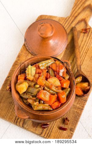 Vegetable stew. Stewed vegetables in a clay pot on a wooden cutting board.