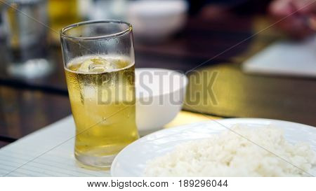 A plate and a glass of beer on the wood table in the restaurant, dinner time with some beer.