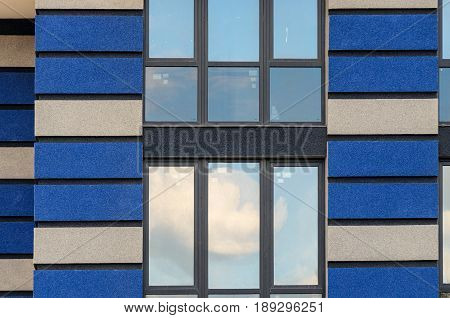Facade with windows of a tall residential building. High-rise buildings modern architecture. Modern high-rise buildings. High-rise building windows.